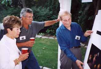 Stanley Wulc (right) shows his still lifes to Ellin and Joe Paquette (left)
