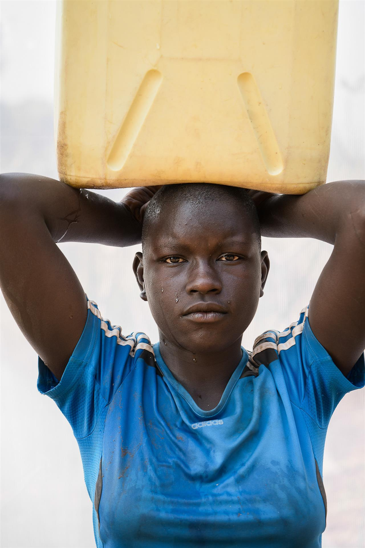 Dan Nelken: A. Sarah: Age 13. Carries a 5 gallon jerrycan of water (41lbs) home three times a day, from the series The Women of Rural Uganda, 2018