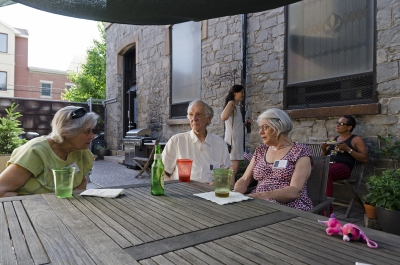 Gwen Gilens (left) converses with photographer Will Brwon and his wife Emily outdoors on the patio. Photo: Stephen Perloff.
