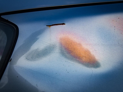 "Laurie Peek: Orange-Pink Cloud on Blue Car, Hastings-on-Hudson, NY, 2014, from the ""Car Parts: Metallic Transports"" series"